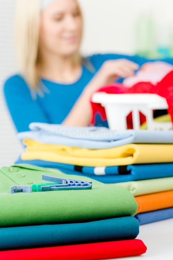 给晒衣夹折叠的洗衣店妇女穿衣 免版税库存照片