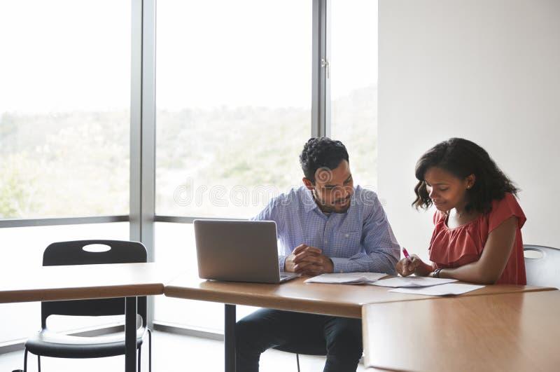 给有膝上型计算机一到一学费的高中家庭教师女学生在书桌 免版税图库摄影