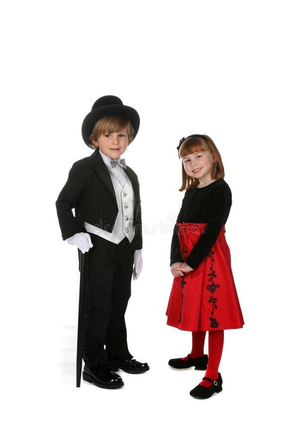 给正式女孩穿衣的男孩 免版税库存图片