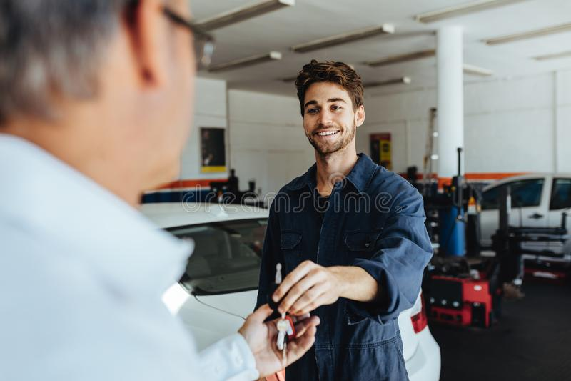 给汽车钥匙的技工顾客在为服务以后 库存照片