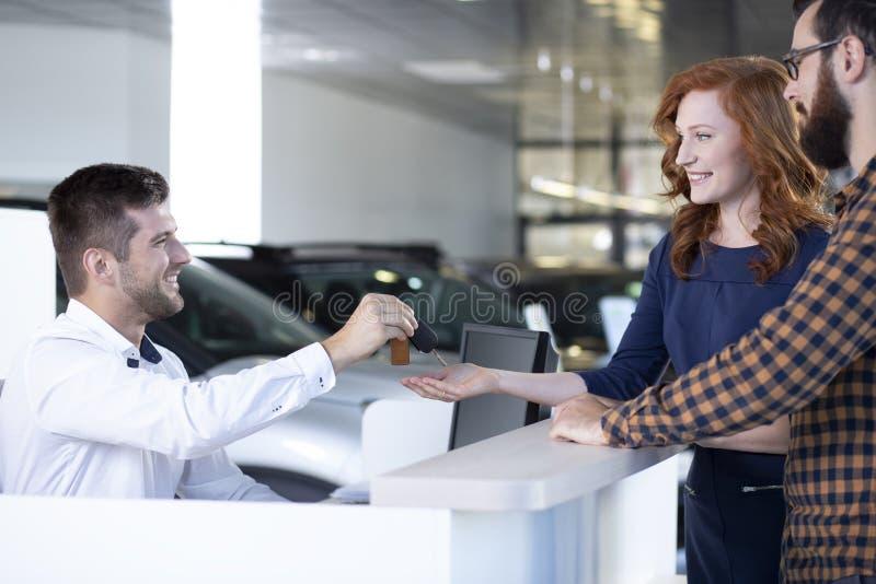给汽车钥匙的车商一对愉快的夫妇在汽车陈列室里 库存照片