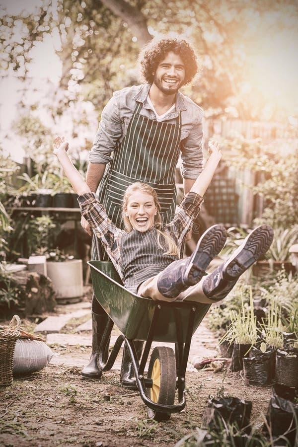 给独轮车乘驾的快乐的人女性花匠 库存照片