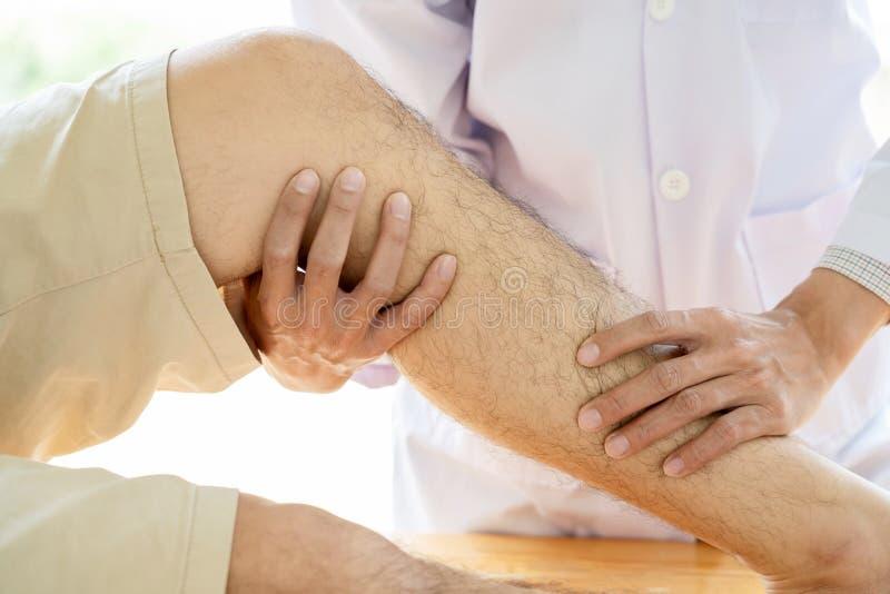 给生理治疗师医生修复咨询的物理疗法行使与患者的腿治疗理疗的诊所的或ho 库存照片