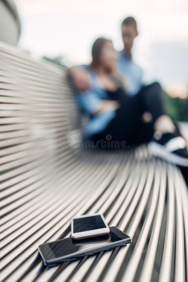 给瘾概念,在长凳的两个智能手机打电话 免版税库存图片