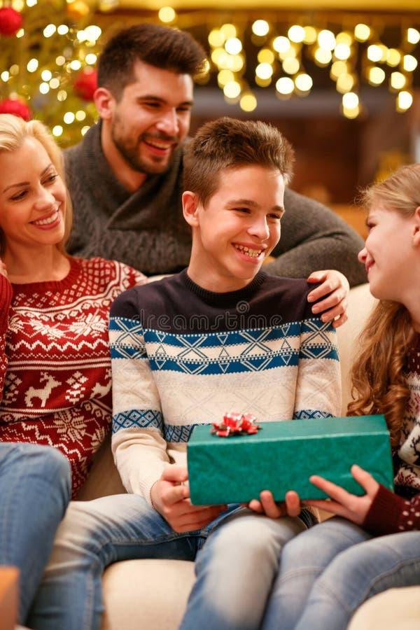 给礼物他的圣诞节的更老的兄弟妹 免版税库存照片