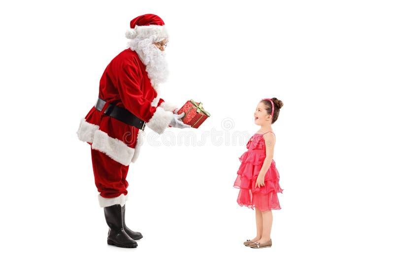 给礼物的圣诞老人一个愉快的小女孩 免版税图库摄影