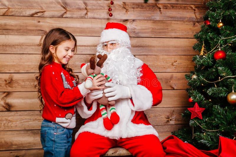 给礼物的圣诞老人项目一个小逗人喜爱的女孩在室内圣诞树附近 库存图片
