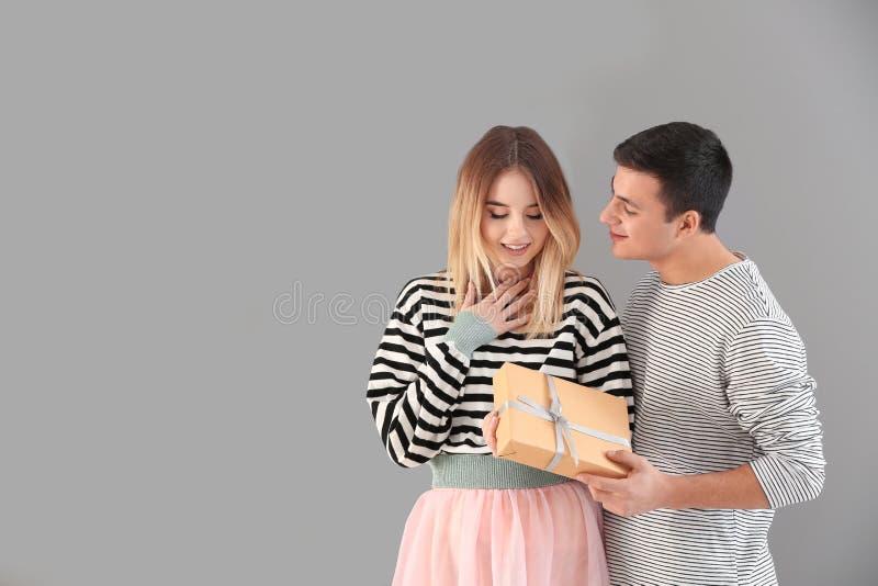 给礼物的年轻人他灰色背景的心爱的女朋友 免版税库存图片