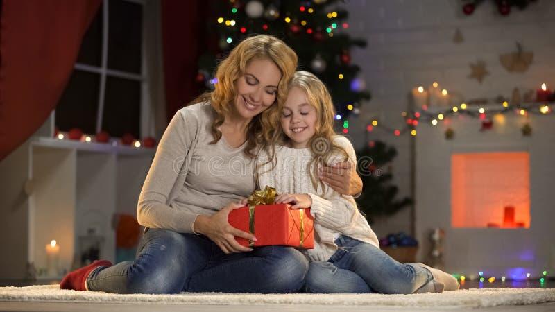 给礼物的母亲爱的女儿、爱和统一性在圣诞节 免版税库存图片