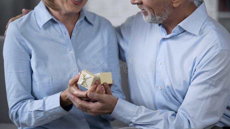 给礼物的资深丈夫妻子,对珍贵的礼物高兴的妇女 免版税库存照片