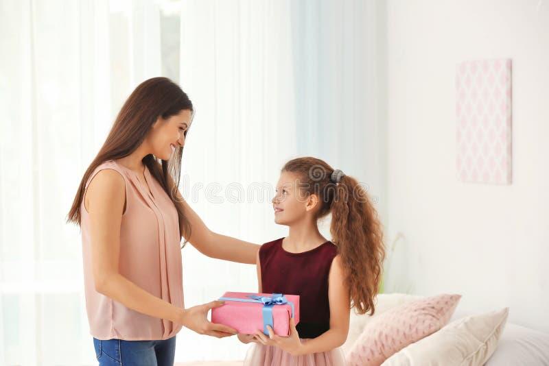 给礼物盒的逗人喜爱的小女孩她的妈妈户内 免版税库存图片