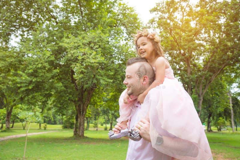 给肩扛乘驾的父亲他的女儿在公园 免版税库存照片