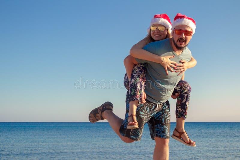 给肩扛的英俊的行家人他的xmas帽子和玻璃的女朋友在海滩海 库存照片