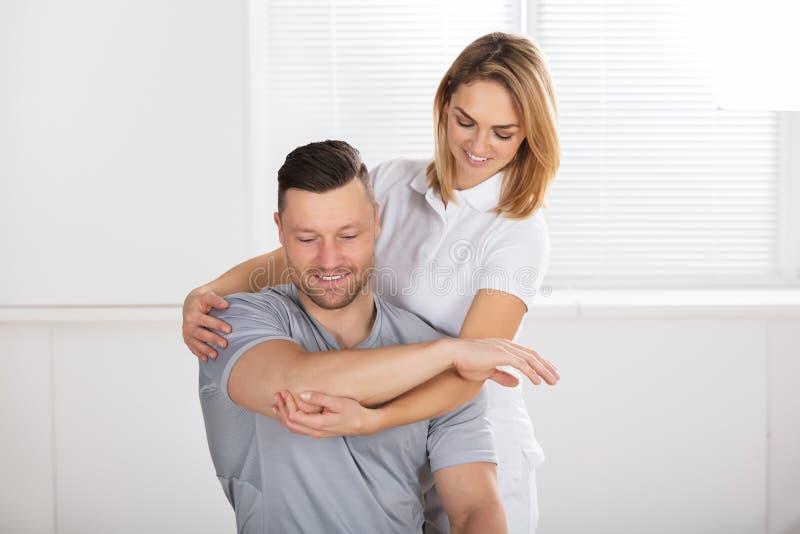 给肩膀锻炼的微笑的女性生理治疗师 免版税库存图片