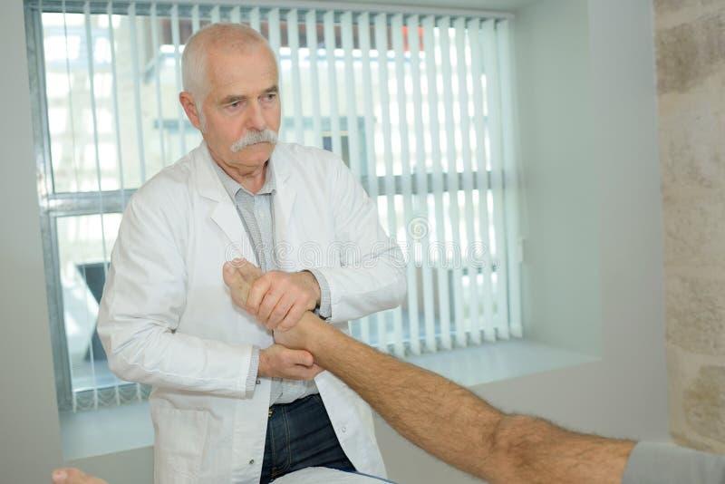 给脚按摩的资深生理治疗师诊所的妇女 图库摄影