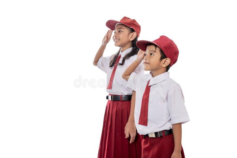 给致敬的小学生佩带的制服印度尼西亚旗子 库存照片