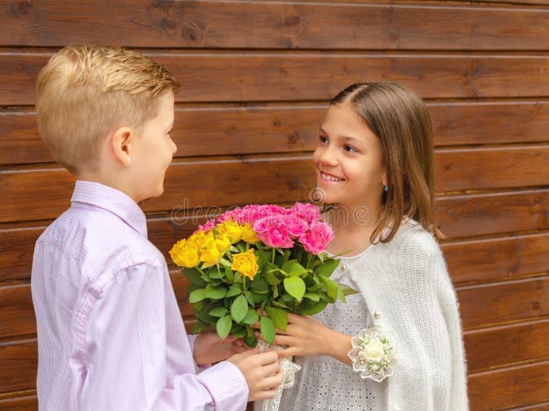 给花束的逗人喜爱的小男孩迷住一点接受黄色和桃红色玫瑰的爱的夫人–微笑的女孩 库存照片
