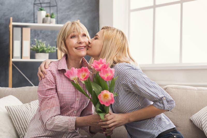 给花的女儿成人母亲 免版税库存照片