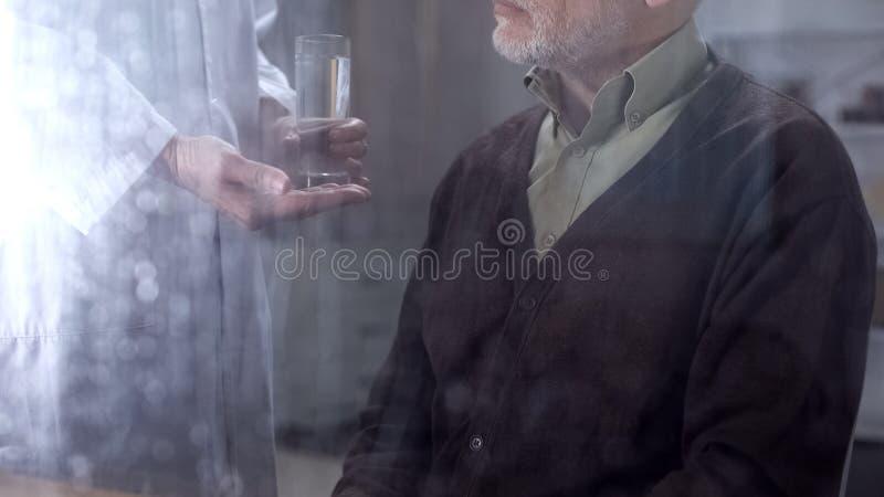 给药片和水玻璃的护士资深男性患者,医院护理,病症 库存图片
