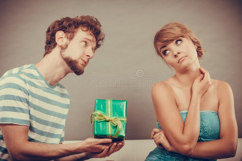 给被触犯的妇女礼物盒的年轻人 免版税图库摄影