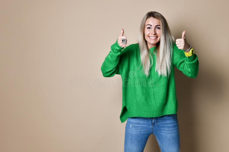 给认同和成功的赞许姿态可爱的年轻女人与愉快的微笑 免版税库存照片