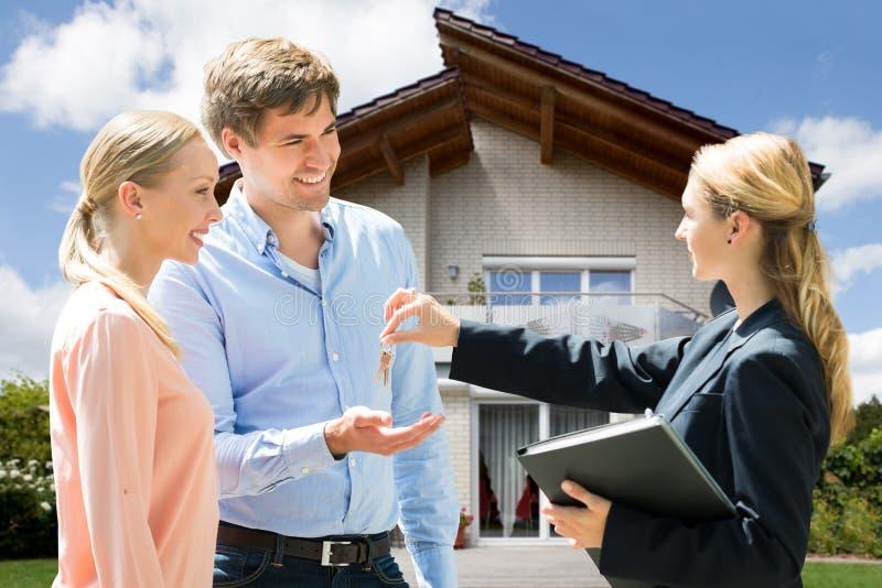 给议院钥匙的不动产房地产经纪商年轻夫妇 免版税图库摄影