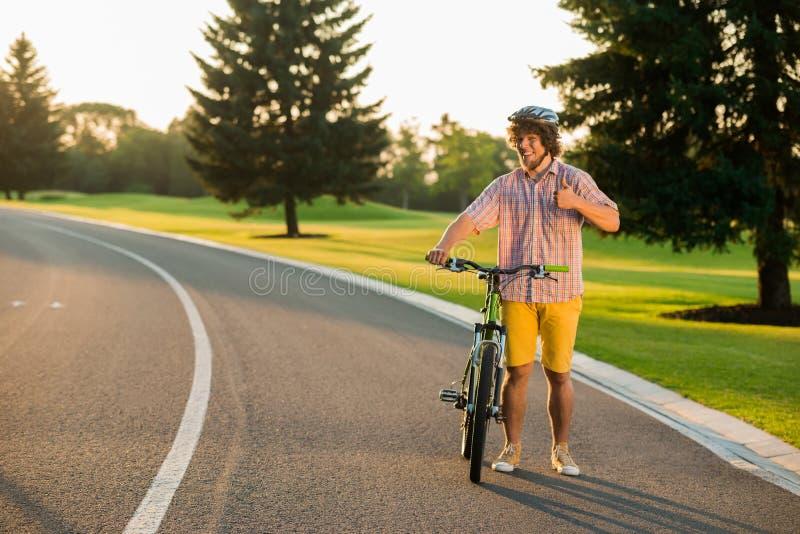 给赞许姿态的逗人喜爱的微笑的骑自行车者 免版税图库摄影