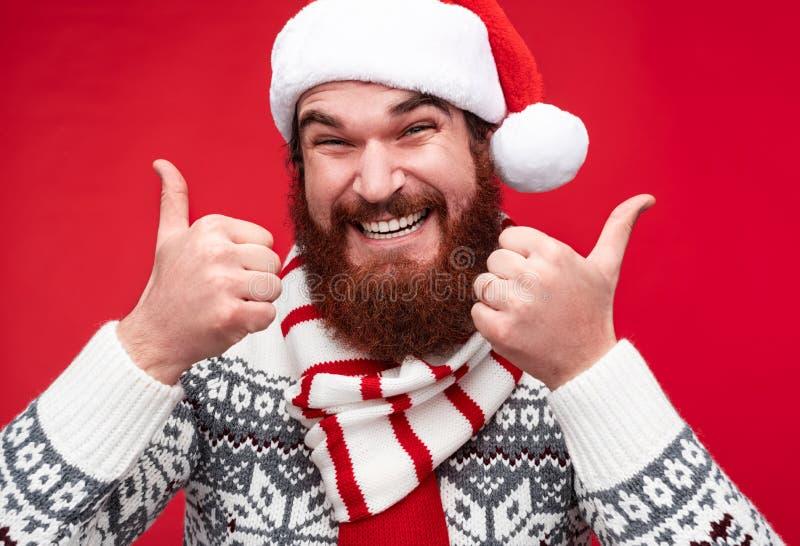 给赞许的冬季衣服和圣诞老人帽子的人 库存照片