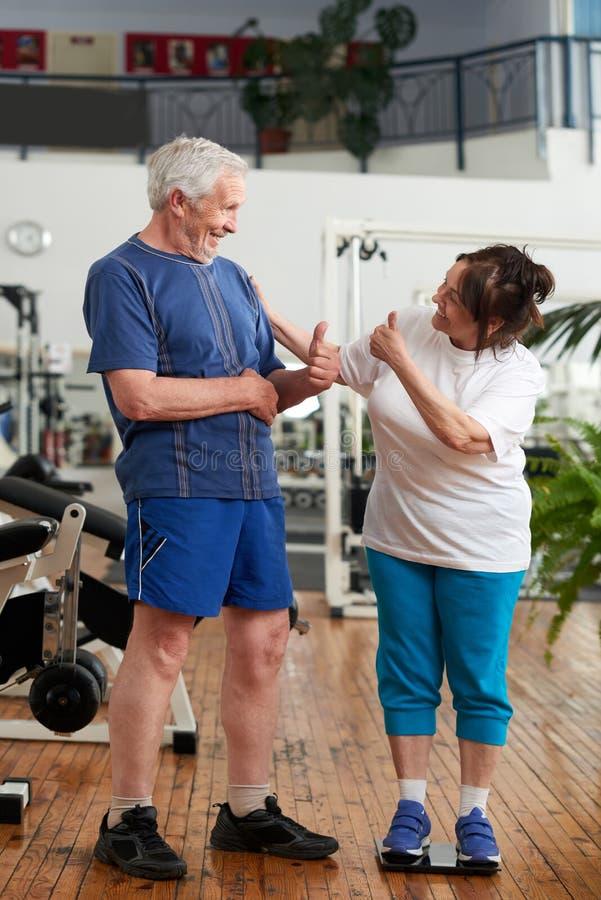 给赞许的资深夫妇在健身房 免版税库存图片