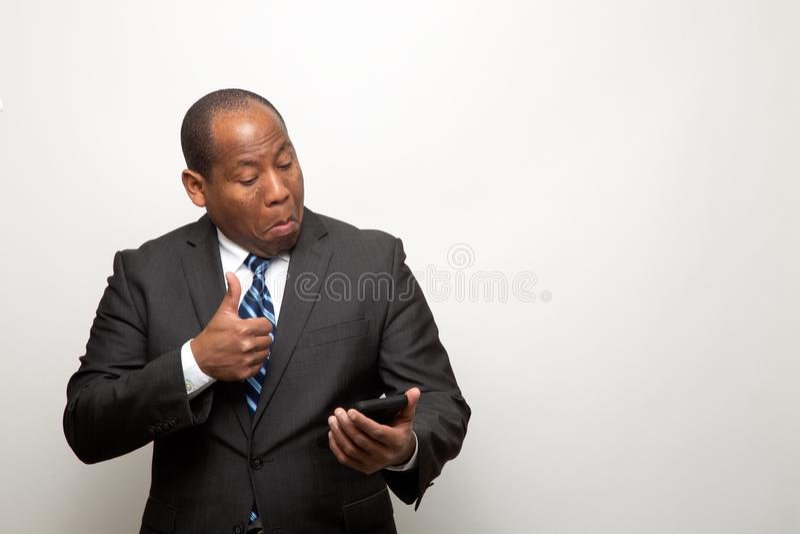 给赞许的非裔美国人的商人通过电话 库存图片