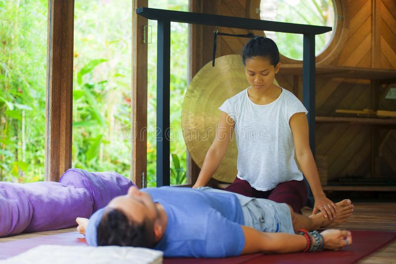 给身体泰国按摩的年轻美丽和异乎寻常的亚裔巴厘语健康治疗师传统的可爱的白种人人 库存照片