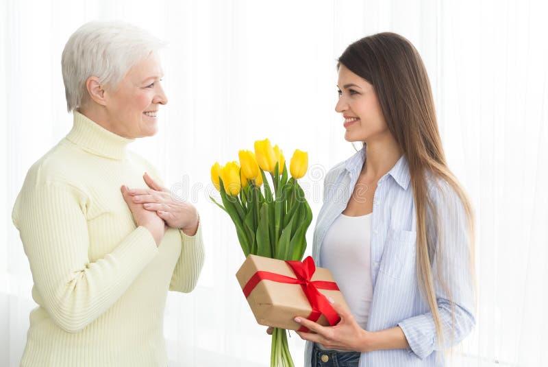 给郁金香和礼物盒的妇女她的成熟母亲 库存照片