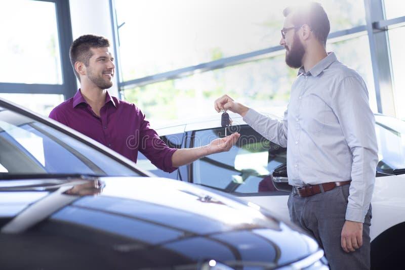 给钥匙的微笑的车商一个成交的沙龙的新的买家 库存照片