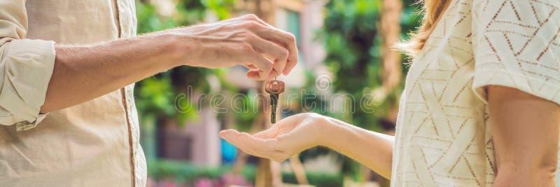 给钥匙的房地产开发商公寓所有者,买卖物产事务 关闭采取从稀土的男性手房子钥匙 免版税库存图片