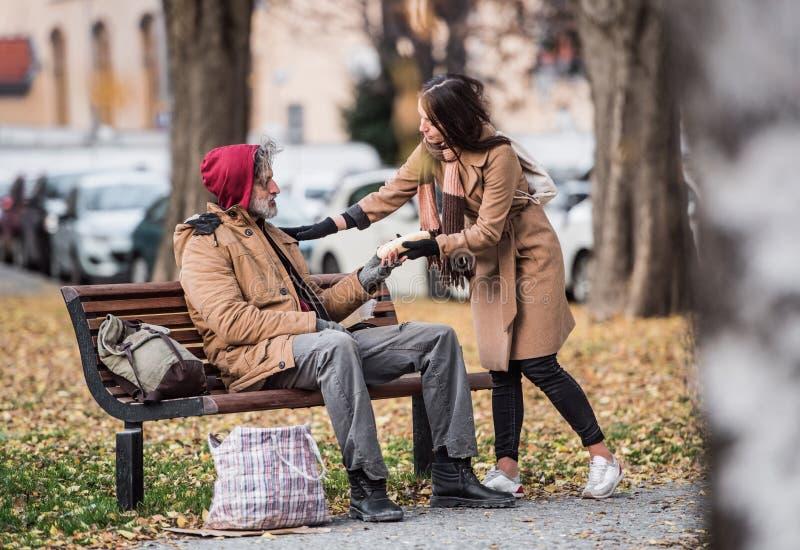 给食物的年轻女人无家可归的叫化子人坐一条长凳在城市 库存图片