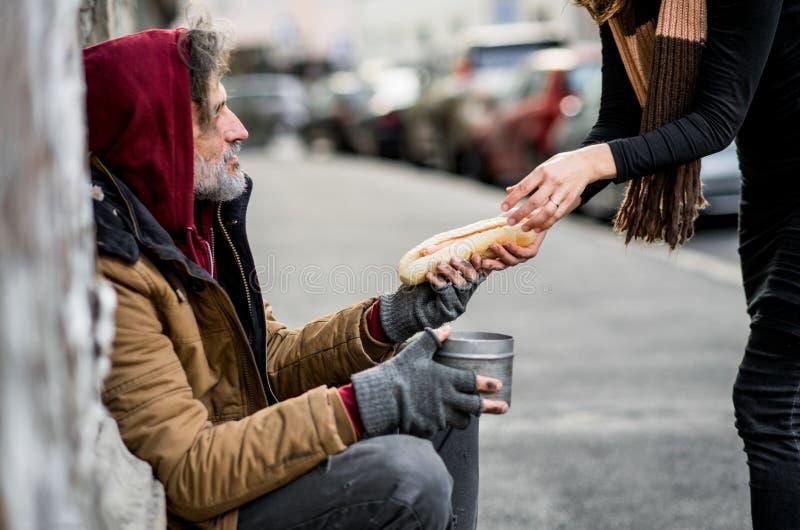 给食物的无法认出的妇女坐在城市的无家可归的叫化子人 免版税库存图片