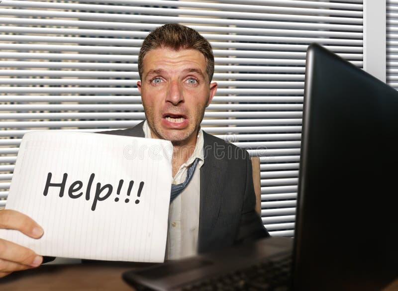 绝望和被注重的商人工作被淹没在感觉办公计算机的书桌无能为力和劳累过度的举行的笔记薄 免版税库存照片