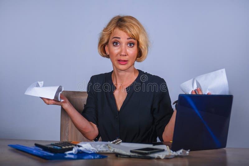 绝望和被注重的女商人工作被淹没在办公桌与举行文书工作的便携式计算机看起来疯狂和 库存照片