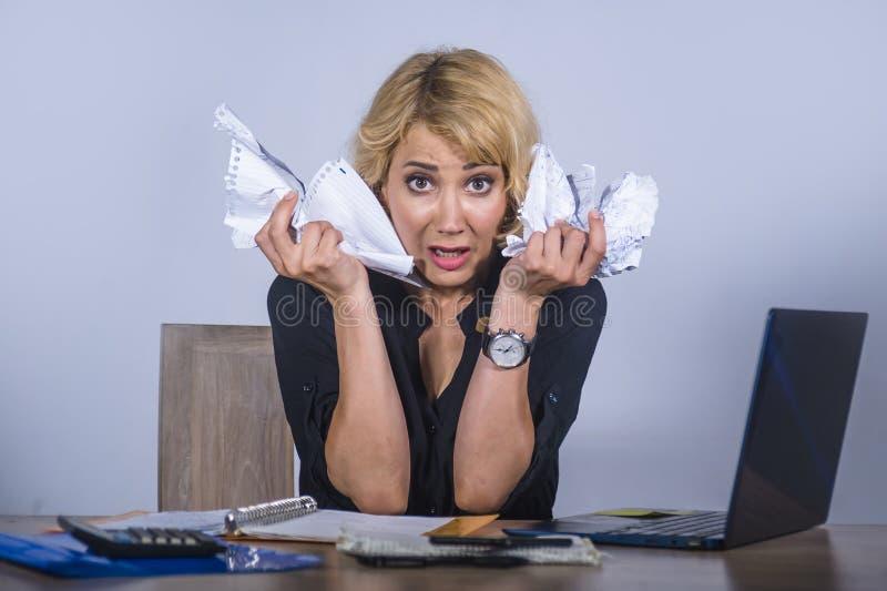 绝望和被注重的女商人工作被淹没在办公桌与举行文书工作的便携式计算机看起来疯狂和 免版税库存图片