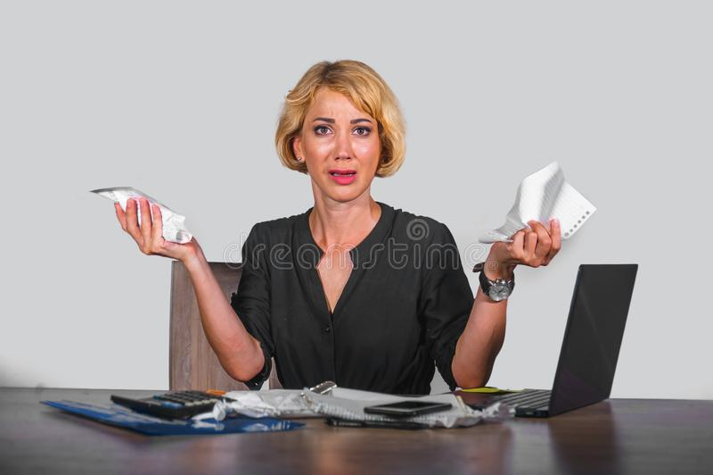 绝望和被注重的女商人工作被淹没在办公桌与举行文书工作的便携式计算机看起来疯狂和 库存图片
