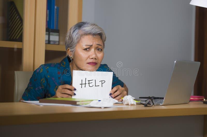 绝望和被注重的有吸引力的中部变老了亚洲妇女藏品笔记薄请求感觉的帮忙劳累过度和被利用的工作 免版税库存图片