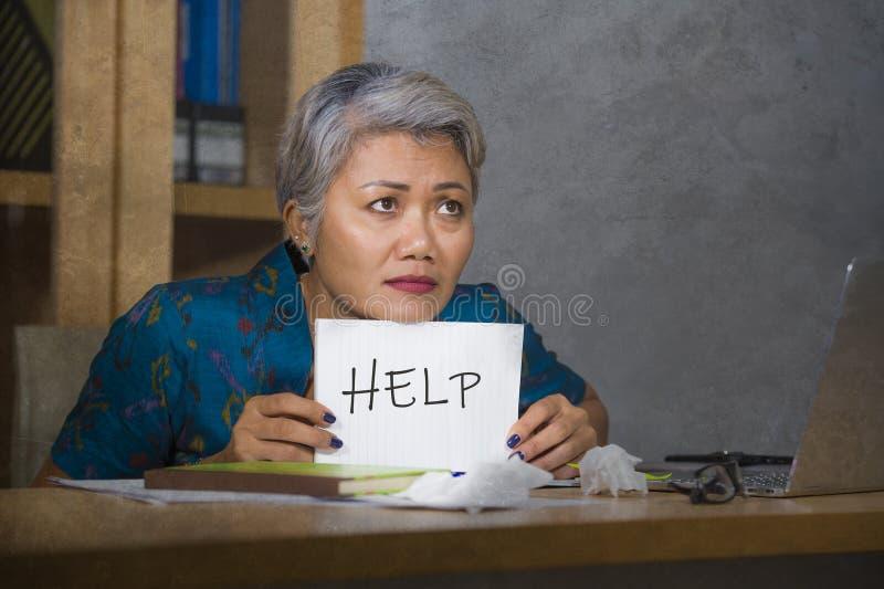 绝望和被注重的有吸引力的中部变老了亚洲妇女藏品笔记薄请求感觉的帮忙劳累过度和被利用的工作 图库摄影
