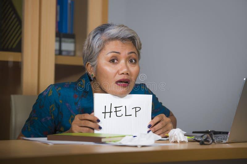 绝望和被注重的有吸引力的中部变老了亚洲妇女藏品笔记薄请求感觉的帮忙劳累过度和被利用的工作 免版税库存照片