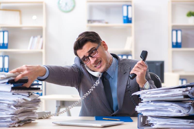 绝望哀伤的雇员在电话中心疲倦了在他的书桌 库存图片