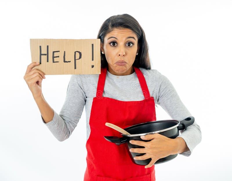 绝望无能为力的无经验的家庭厨师妇女画象请求佩带红色围裙的帮忙学会烹调在烹饪课 库存图片