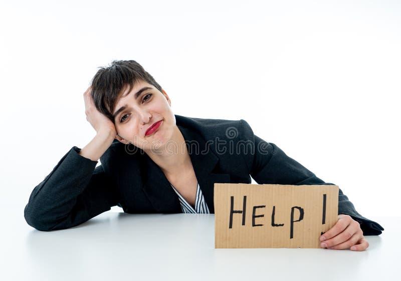 绝望美丽的年轻的女商人被淹没和拿着帮助标志 免版税库存图片