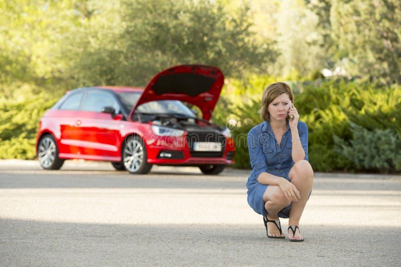 绝望迷茫的妇女搁浅与拜访手机的残破的发动机崩溃事故 免版税库存图片