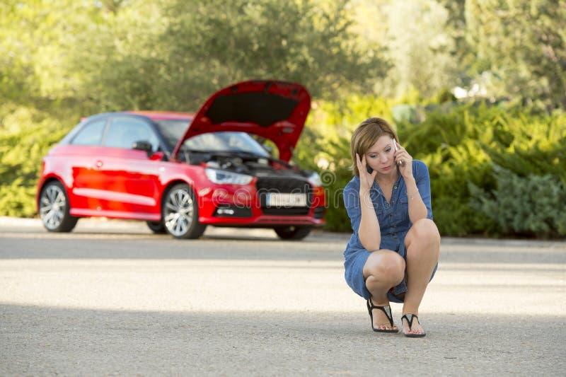 绝望迷茫的妇女搁浅与拜访手机的残破的发动机崩溃事故 库存图片