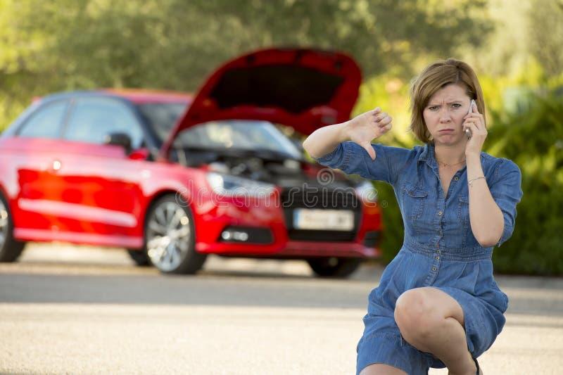 绝望迷茫的妇女搁浅与拜访手机的残破的发动机崩溃事故 库存照片