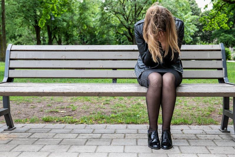 绝望,哭泣的妇女坐长凳在公园 免版税库存图片